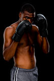 Portrait of a shirtless muscular boxer in defensive stance. Over black background Stock Photo