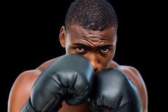 Portrait of a shirtless muscular boxer in defensive stance. Over black background Royalty Free Stock Photo