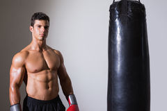 Portrait of a shirtless muscular boxer with punching bag Royalty Free Stock Photos