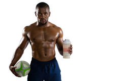 Portrait of shirtless sportsman with rugby ball holding drinking bottle Stock Photos
