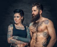 Portrait of shirtless, tattooed bearded male and brunette female with tattoo ink on her torso. Portrait of shirtless, tattooed bearded hipster male and brunette Royalty Free Stock Photography