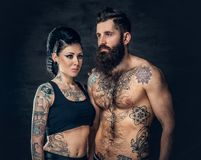 Portrait of shirtless, tattooed bearded male and brunette female with tattoo ink on her torso. Portrait of shirtless, tattooed bearded hipster male and brunette Stock Image