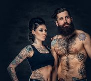 Portrait of shirtless, tattooed bearded male and brunette female with tattoo ink on her torso. Portrait of shirtless, tattooed bearded hipster male and brunette Stock Images