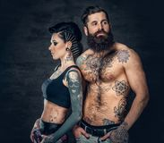 Portrait of shirtless, tattooed bearded male and brunette female with tattoo ink on her torso. Portrait of shirtless, tattooed bearded hipster male and brunette Royalty Free Stock Photo