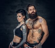 Portrait of shirtless, tattooed bearded male and brunette female with tattoo ink on her torso. Portrait of shirtless, tattooed bearded hipster male and brunette Stock Photography