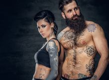 Portrait of shirtless, tattooed bearded male and brunette female with tattoo ink on her torso. Portrait of shirtless, tattooed bearded hipster male and brunette Royalty Free Stock Photos