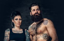 Portrait of shirtless, tattooed bearded male and brunette female with tattoo ink on her torso. Portrait of shirtless, tattooed bearded hipster male and brunette Stock Photos