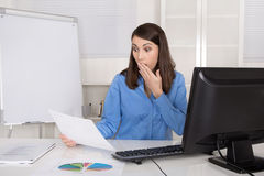 Portrait of shocked and amazed business woman sitting at desk. Stock Image