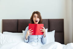 Portrait of a shocked astonished woman in pajamas holding book Stock Images