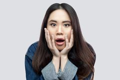 Portrait of shocked beautiful brunette asian young woman in blue denim jacket with makeup standing touching face and looking at. Camera with big eyes. studio royalty free stock photos