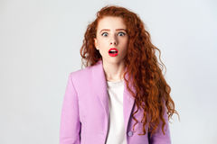 Portrait of shocked beautiful business woman with red - brown hair and makeup in pink suit. looking at camera Royalty Free Stock Photography