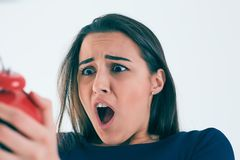 Portrait of shocked and angry woman with alarm clock over white background. Stock Photos