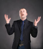 Portrait of a shocked business man. Holding his hands up on a gray background Stock Images