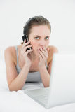 Portrait of a shocked casual woman using cellphone and laptop Stock Image