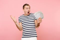 Portrait of shocked excited young man in striped t-shirt holding bundle lots of dollars, cash money, ardor gesture on. Portrait of smiling excited young man in stock photo
