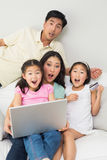 Portrait of shocked family of four doing online shopping Stock Image