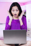 Portrait of shocked girl with laptop Stock Photo