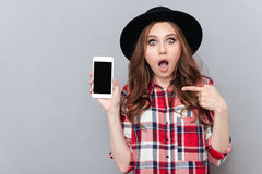 Portrait of a shocked girl in plaid shirt pointing finger. Portrait of a shocked casual girl in plaid shirt pointing finger at blank screen mobile phone isolated Stock Image