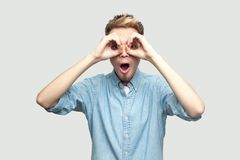 Portrait of shocked handsome young man in light blue shirt standing with hands on eyes binoculars gesture and looking at camera. With surprised face. indoor royalty free stock photography