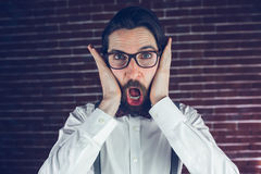 Portrait of shocked man. Against brick wall royalty free stock image