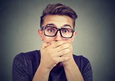 Portrait of a shocked man covering his mouth with hands. Portrait of a shocked young man covering his mouth with hands Royalty Free Stock Images