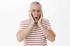 Portrait of shocked man looking astonished and excited at camera with dropped jaw holding hands pressed on cheeks. Learning surprising unexpected rumor staring stock photos