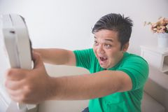 Shocked obese man while looking at a weight scale. Portrait of shocked obese man while looking at a weight scale Stock Images