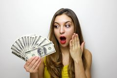 Portrait of a shocked pretty girl looking at bunch of money banknotes isolated over white background royalty free stock image