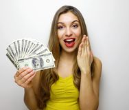 Portrait of a shocked pretty girl looking at camera with money banknotes isolated over white background royalty free stock photo