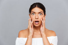 Portrait of shocked pretty young woman touching her face Stock Photography