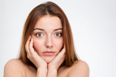 Portrait of shocked pretty young woman touching her face Royalty Free Stock Photography