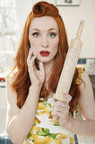 Portrait of a shocked redheaded woman with a rolling pin Stock Images