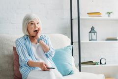 Portrait of shocked senior woman. With remote control watching tv on sofa at home royalty free stock images
