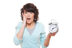 Portrait of shocked woman with alarm clock. Over white background Stock Photos