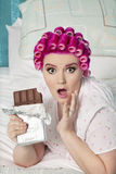 Portrait of shocked woman with chocolate lying on bed Royalty Free Stock Photos