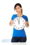 Portrait of shocked woman with clock. Over white background Royalty Free Stock Image