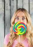 Portrait of shocked woman covering mouth with candy against wooden wall Royalty Free Stock Photos
