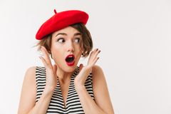 Portrait of a shocked woman dressed in red beret. Screaming and looking away isolated over white background Royalty Free Stock Image