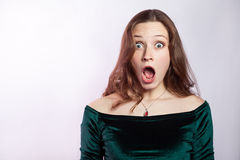 Portrait of shocked woman with freckles and classic green dress. Stock Photos