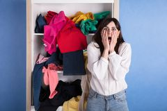 Portrait Of A Shocked Woman. In Front Of Scattered Clothes On Shelf stock photo
