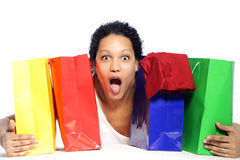 Shocked woman. Portrait of shocked woman holding colorful shopping bags Stock Images
