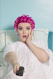 Portrait of shocked woman holding remote with hair curlers sitting on bed Stock Photography