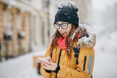 Portrait of shocked woman looking at mobile phone in hand she has some good news message photos with stunned emotion on stock photography