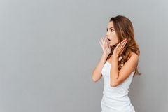 Portrait of shocked woman with mouth open looking away. Isolated on a gray background Stock Photos