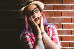 Portrait of shocked woman in spectacles. Against brick wall Stock Images