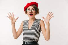 Portrait of a shocked woman wearing red beret. And eyeglasses looking at camera isolated over white background Stock Photography