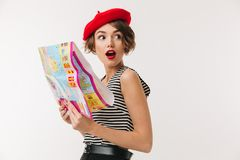 Portrait of a shocked woman wearing red beret. Holding travel map guide and looking away isolated over white background Royalty Free Stock Photos