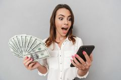 Portrait of a shocked young business woman. Looking at mobile phone while holding bunch of money banknotes isolated over white background Royalty Free Stock Photography