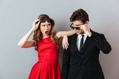 Portrait of a shocked young couple dressed in formal wear. And sunglasses posing while standing and looking at each other over gray wall background Stock Photo