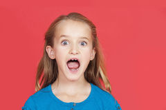 Portrait of shocked young girl with mouth open against red background Stock Photography